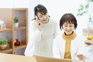 スマートフォンで通話する娘とネットショッピングする母の写真素材 [FYI04803844]