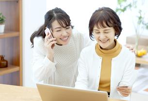 スマートフォンで通話する娘とネットショッピングする母の写真素材 [FYI04803845]