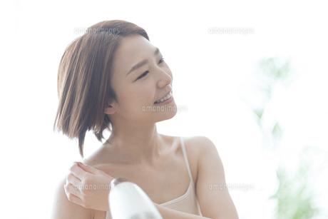 ドライヤーで髪を乾かす女性の写真素材 [FYI04806233]