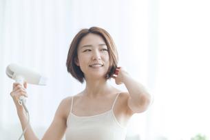 ドライヤーで髪を乾かす女性の写真素材 [FYI04806234]