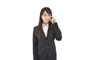 目に指を当て悲しむスーツの女性 白背景の写真素材 [FYI04807467]