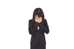 悲しんで顔を覆っているスーツの女性 白背景の写真素材 [FYI04807468]