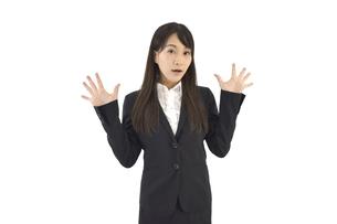 両手を広げて驚くスーツの女性 白背景の写真素材 [FYI04807469]