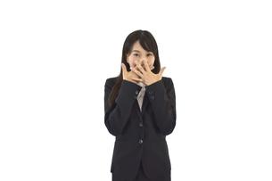 両手を顔に当てて驚いているスーツの女性の写真素材 [FYI04807470]