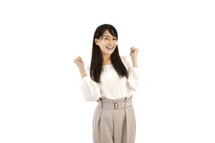 ガッツポーズで成功を喜んでいるカジュアルの女性 白背景の写真素材 [FYI04807472]