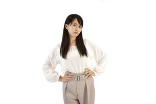 両手を腰に置いて怒るカジュアル女性 白背景の写真素材 [FYI04807473]
