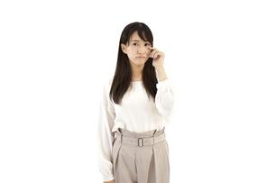 目に指を当て悲しむカジュアルの女性 白背景の写真素材 [FYI04807475]