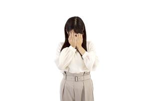 悲しんで顔を覆っているカジュアルの女性 白背景の写真素材 [FYI04807476]