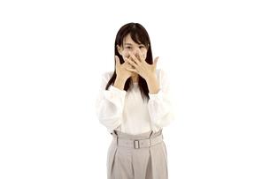 両手で口を覆って驚いているカジュアルの女性 白背景の写真素材 [FYI04807477]