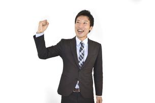 ガッツポーズで成功を喜んでいるスーツの男性 白背景の写真素材 [FYI04807478]