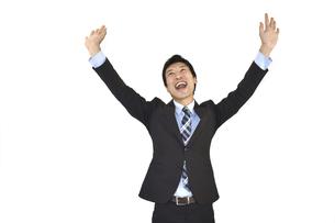 両手を上げてバンザイしているスーツの男性 白背景の写真素材 [FYI04807479]