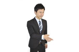 注意、指示をしているスーツの男性 白背景の写真素材 [FYI04807480]