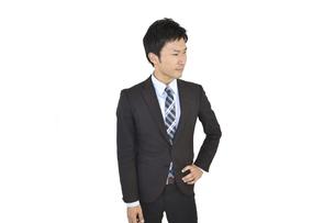 手を腰に当てて考えているスーツの男性 白背景の写真素材 [FYI04807481]