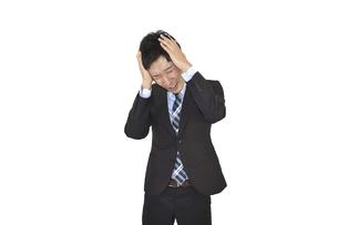 両手で頭を抱えて悩んでいるスーツの男性 白背景の写真素材 [FYI04807483]
