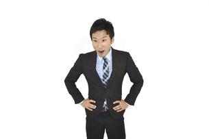 両手を腰に置いて驚くスーツの男性 白背景の写真素材 [FYI04807485]