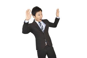 両手を上げて驚くスーツの男性 白背景の写真素材 [FYI04807486]