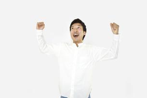 ガッツポーズで成功を喜んでいるカジュアルの男性 白背景の写真素材 [FYI04807494]