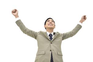 両手を上げて喜んでいるスーツの男性 白背景の写真素材 [FYI04807821]