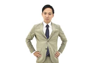 両手を腰に置いて怒るスーツの男性 白背景の写真素材 [FYI04807823]