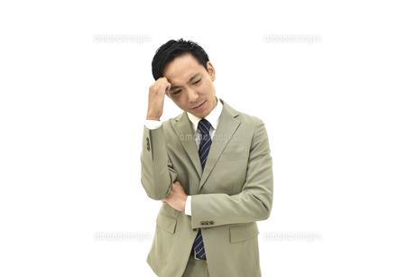 うまくいかず悩んでいるスーツの男性 白背景の写真素材 [FYI04807824]