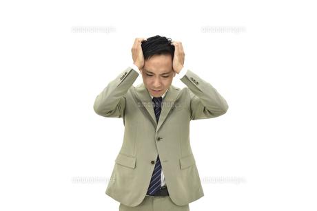 両手で頭を抱えて悩んでいるスーツの男性 白背景の写真素材 [FYI04807825]