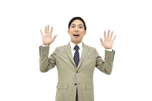 両手を上げて驚くスーツの男性2 白背景の写真素材 [FYI04807826]