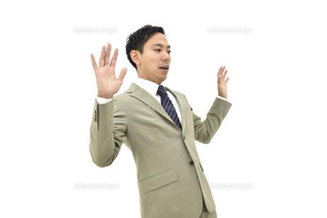 両手を上げて驚くスーツの男性1 白背景の写真素材 [FYI04807827]