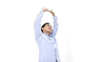 両手を上げて背伸びをしているカジュアルの男性 白背景の写真素材 [FYI04807828]