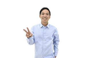 ピースをして喜んでいるカジュアルの男性 白背景の写真素材 [FYI04807829]