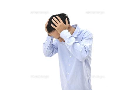 両手で頭を抱えて悩んでいるカジュアルの男性 白背景の写真素材 [FYI04807833]