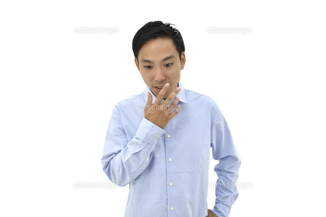 口に手を当てて驚くカジュアルの男性 白背景の写真素材 [FYI04807834]