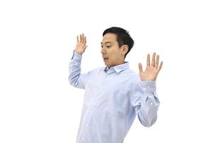 両手を広げて驚くカジュアルの男性 白背景の写真素材 [FYI04807835]