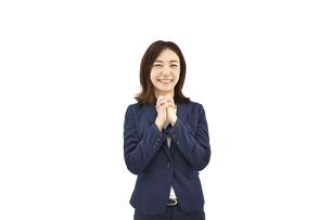 両手を組んで喜ぶスーツの女性 白背景の写真素材 [FYI04807933]
