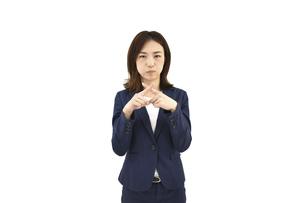 不正解とバツをしているスーツの女性 白背景の写真素材 [FYI04807936]
