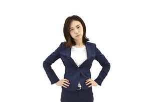 両手を腰に置いて怒るスーツの女性 白背景の写真素材 [FYI04807938]