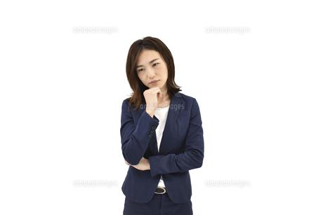 悩んでいるスーツの女性 白背景の写真素材 [FYI04807939]