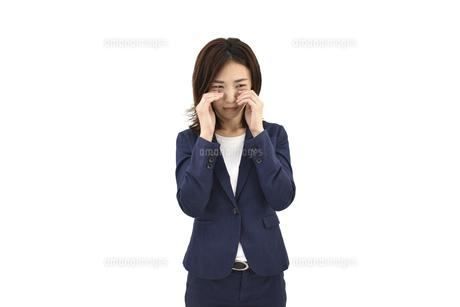 目に指を当てて悲しむスーツの女性 白背景の写真素材 [FYI04807941]