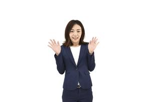 両手を広げて驚くスーツの女性 白背景の写真素材 [FYI04807942]