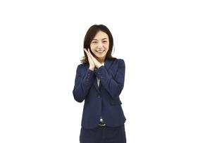 両手を合わせて喜んでいるスーツの女性 白背景の写真素材 [FYI04807944]