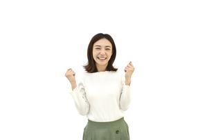 ガッツポーズで成功を喜んでいるカジュアルの女性 白背景の写真素材 [FYI04807948]