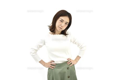 両手を腰に置いて怒るカジュアル女性 白背景の写真素材 [FYI04807951]