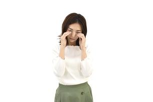 目に手を当てて悲しんでいるカジュアルの女性 白背景の写真素材 [FYI04807953]