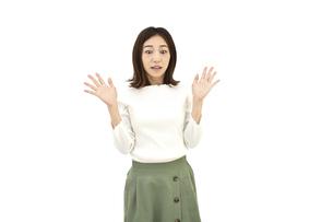 両手を広げて驚くカジュアルの女性 白背景の写真素材 [FYI04807954]