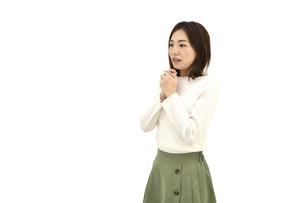 両手を組んで驚くカジュアルの女性 白背景の写真素材 [FYI04807955]