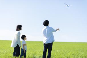 草原で模型飛行機を飛ばすファミリーの写真素材 [FYI04808380]
