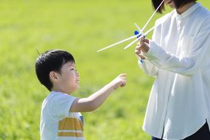 草原で模型飛行機で遊ぶ親子の写真素材 [FYI04808387]