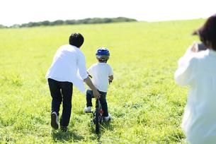草原で自転車に乗る子供の後ろ姿の写真素材 [FYI04808414]