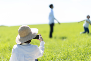 草原で遊ぶ家族を撮影するお母さんの写真素材 [FYI04808421]
