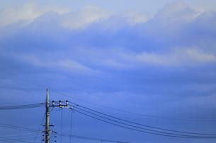 電信柱と電線を三つ編みを結ったような妙な雲が覆う上空の光景の写真素材 [FYI04809078]