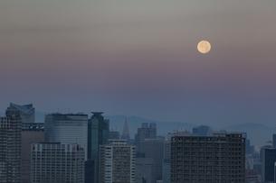 早朝の月と都心のビル群の写真素材 [FYI04810430]